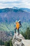 Viajero del hombre que se coloca en un top de la montaña Fondo del bosque imagenes de archivo