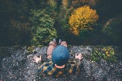 Viajero del hombre que se sienta en el borde del puente del acantilado imagen de archivo