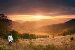 Viajero en el fondo de la puesta del sol de la montaña Imágenes de archivo libres de regalías