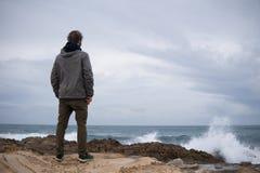 Viajero en las rocas cerca del mar que considera lejos el horizonte Rocky Atlantic Ocean Coastline y clima tempestuoso imagen de archivo