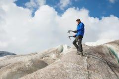 Viajero en un casquillo y las gafas de sol que se colocan con el hacha de hielo en las montañas nevosas en el glaciar Viajero en  imagen de archivo