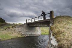 Viajero en un puente cerca de la cascada de Gluggafoss imagen de archivo libre de regalías