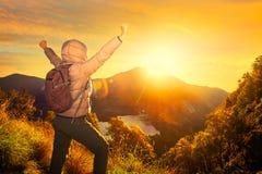 Viajero feliz con la mochila que se coloca en una roca con la mano aumentada Fotografía de archivo