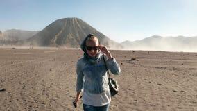 Viajero feliz de la mujer que camina en un desierto polvoriento volcánico cerca del soporte hermoso Bromo en Java Oriental almacen de video