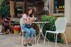 Viajero feliz de la mujer que comprueba la cámara que se sienta en café del aire libre en ciudad retra del vintage fotos de archivo
