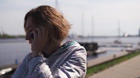 Viajero feliz que habla sobre su teléfono en un restaurante - pelo marrón ondulado, luz que lleva de la mujer femenina caucásica  almacen de video