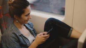 Viajero femenino casual que se sienta en el asiento del tren con la pierna contra la pared usando la red social app del smartphon almacen de video