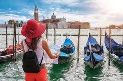 Viajero femenino delante de las góndolas del cuadrado del ` s de St Mark en Venecia imagen de archivo