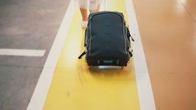 Viajero femenino elegante joven que camina a través del aparcamiento del aeropuerto con la maleta La muchacha viene el vacaciones Imagen de archivo libre de regalías