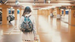 Viajero femenino elegante joven que camina a través del aparcamiento del aeropuerto con la maleta La muchacha viene el vacaciones Imagen de archivo