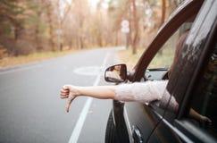 Viajero femenino en el camino que sujeta el pulgar hacia abajo Vacaciones de la caída, días de fiesta, viaje, viaje por carretera Imagen de archivo libre de regalías