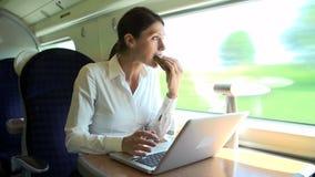 Viajero femenino en el tren usando el ordenador portátil mientras que come el bocadillo metrajes