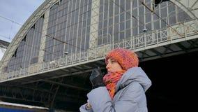 Viajero femenino que espera en el ferrocarril durante día de invierno soleado pero frío Concepto del viaje almacen de metraje de vídeo