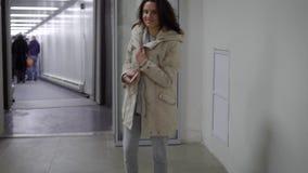 Viajero femenino que sale de un aeropuerto con una mochila almacen de metraje de vídeo
