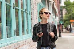 Viajero femenino que usa el guite elegante del app del teléfono en viaje de fin de semana de la rotura de ciudad a Nueva York Imagenes de archivo
