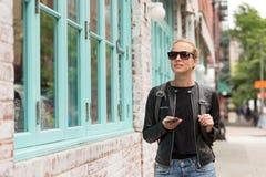 Viajero femenino que usa el guite elegante del app del teléfono en viaje de fin de semana de la rotura de ciudad a Nueva York Foto de archivo libre de regalías