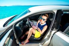 Viajero joven con el mapa que se sienta en el coche Imagen de archivo