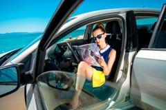 Viajero joven con el mapa que se sienta en el coche Fotografía de archivo libre de regalías