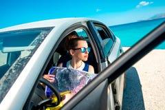 Viajero joven con el mapa que se sienta en el coche Fotos de archivo libres de regalías