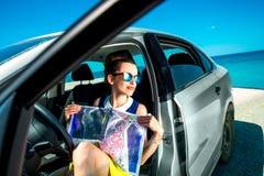 Viajero joven con el mapa que se sienta en el coche Foto de archivo libre de regalías