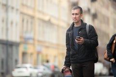 Viajero joven con el teléfono móvil en la calle Fotos de archivo