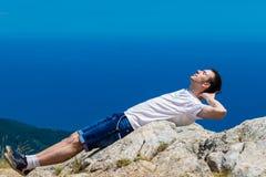 Viajero joven con los pulgares para arriba en un pico de montaña con el mar y el cielo azul en el fondo, caminando Fotografía de archivo libre de regalías