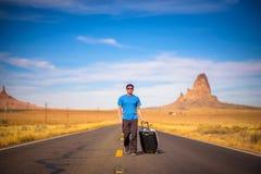 Viajero joven con una maleta que camina en un camino en Arizona Imagenes de archivo