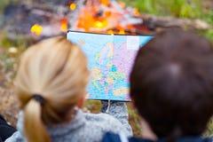 Viajero joven de los pares que mira el mapa Un hombre y una mujer que sientan el ne Foto de archivo