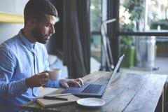 Viajero joven del blogger del inconformista en una chaqueta del dril de algodón usando el ordenador portátil y el wifi modernos Fotografía de archivo libre de regalías