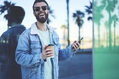 Viajero joven del blogger del inconformista en una chaqueta del dril de algodón usando Internet inalámbrico rápido en la itineran Fotos de archivo libres de regalías