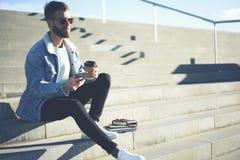 Viajero joven del blogger del inconformista en una chaqueta del dril de algodón vía smartphone y la conexión inalámbrica 5G Imagen de archivo libre de regalías