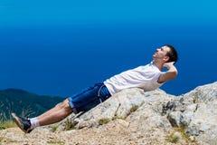 Viajero joven en un pico de montaña con el mar y cielo azul en el fondo, caminando Imagen de archivo