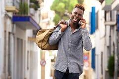 Viajero masculino afroamericano de risa que camina y que habla en el teléfono móvil Fotos de archivo