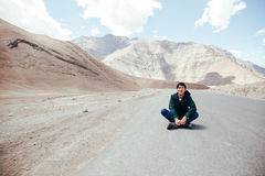 Viajero masculino asiático joven que se sienta en el medio del camino vacío con la libertad y la alegría en Leh, Ladakh, la India Fotografía de archivo libre de regalías
