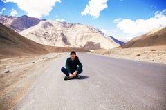 Viajero masculino asiático joven que se sienta en el medio del camino vacío con la libertad y la alegría en Leh, Ladakh, la India Fotos de archivo libres de regalías