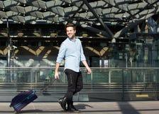Viajero masculino feliz que camina con la maleta Imagen de archivo libre de regalías