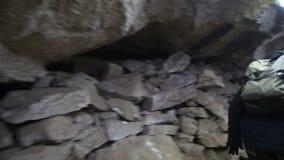 Viajero masculino que camina a través del túnel apretado dentro de la cueva, visión trasera metrajes