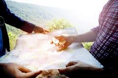 Viajero masculino que lleva a cabo un compás y que mira el mapa Fotos de archivo