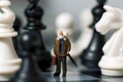 Viajero miniatura y ajedrez de la muñeca Viejo viajero en tablero de ajedrez Imágenes de archivo libres de regalías