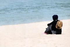 Viajero musulmán de la muchacha en el hijab que se sienta en la playa fotos de archivo