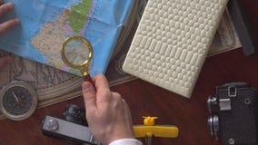 Viajero muy cuidadosamente con una lupa que estudia un mapa y que piensa adonde él irá metrajes