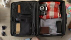 Viajero que embala su maleta, poniendo el monedero, el pasaporte con los boletos y el dinero almacen de metraje de vídeo
