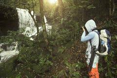 Viajero que fotografía con la mochila y que goza de una cascada Fotos de archivo