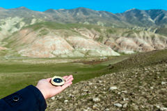 Viajero que lleva a cabo un compás en montañas Foto de archivo