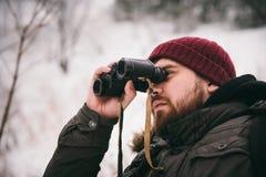 Viajero que mira a través de los prismáticos en el invierno Foto de archivo libre de regalías