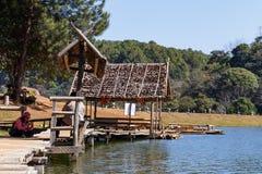 Viajero que se relaja en el puente y la choza de bambú en el lago Imagen de archivo libre de regalías