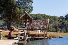 Viajero que se relaja en el puente y la choza de bambú en el lago Foto de archivo