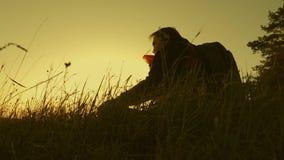 Viajero que se sienta encima de un caf? de consumici?n de la colina en termo El turista bebe puesta del sol caliente del t? y de  almacen de metraje de vídeo