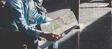 Viajero que se sienta y que mira en el mapa para el tren que espera la estación de tren Fotografía de archivo