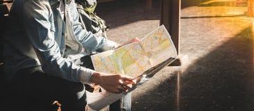 Viajero que se sienta y que mira en el mapa para el tren que espera la estación de tren Imagen de archivo libre de regalías